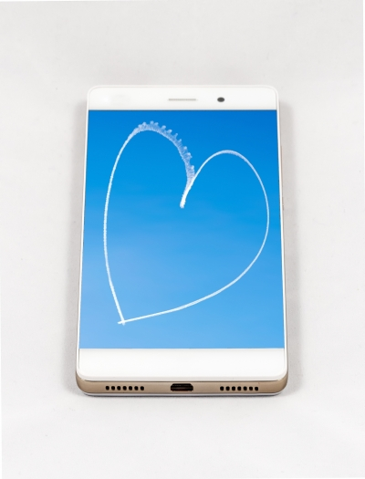 Modern smartphone with full screen picture of a heart written in the sky