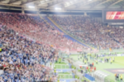 Defocused background with supporters in the stadium for football match