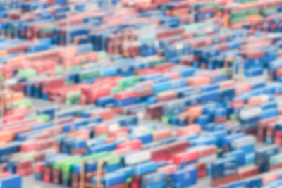 Defocused background of shipping containers stacked on a commercial port
