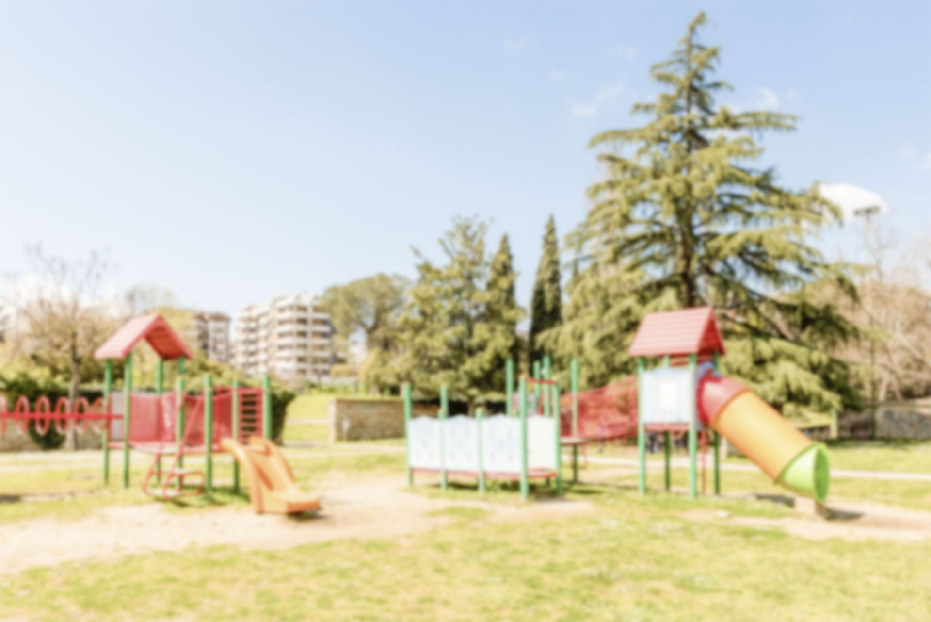 Defocused background of colorful playground for kids in public park