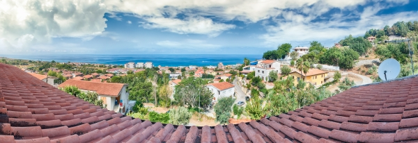 Panoramic view over roof tiles and the coastline, Calabria, Italy