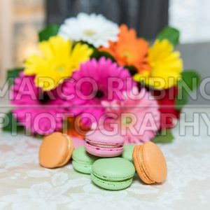 Colorful mix of macarons with a background of gerbers