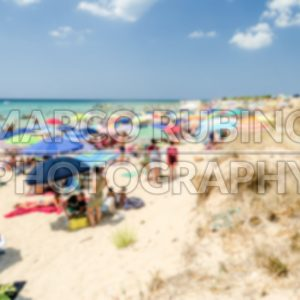 Defocused background of a crowded beach in Salento, Apulia, Italy