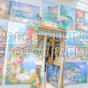 Defocused background with a wall full of paintings