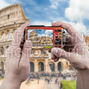 Hands on camera taking picture of  Colosseum in Rome, Italy