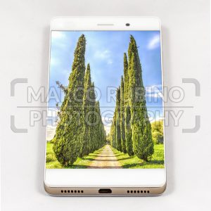 Modern smartphone displaying full screen picture of cypresses, Italy