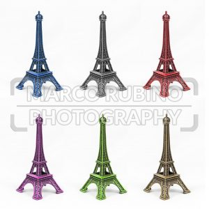 Six multicolored Eiffel Tower models, isolated on white background