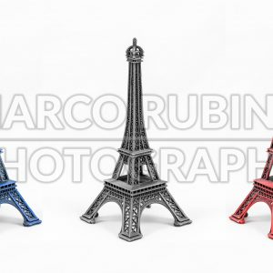 Three multicolored Eiffel Tower models, isolated on white background