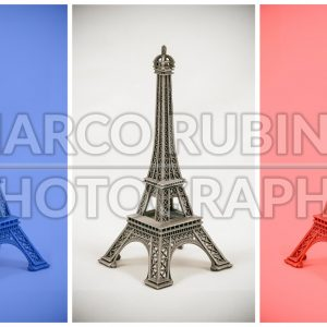 Three multicolored Eiffel Tower models on french flag