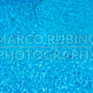 Defocused background with blue water surface of a swimming pool