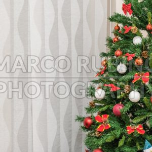 Detail of a Christmas tree against a textured curtain