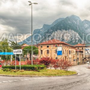 City intersection with scenic mountain in the background, Lecco, Italy