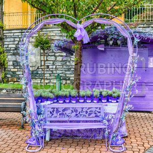 Scenic heart-shaped violet bench decorated with flowers and laces