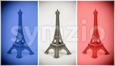 Three multicolored Eiffel Tower models on french flag Stock Photo