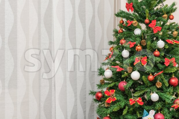 Detail of a Christmas tree against a textured curtain Stock Photo