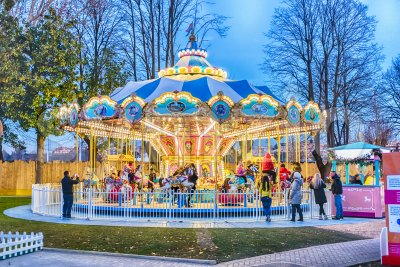 Old fashioned carousel in amusement park at dusk Stock Photo