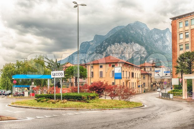 City intersection with scenic mountain in the background, Lecco, Italy Stock Photo