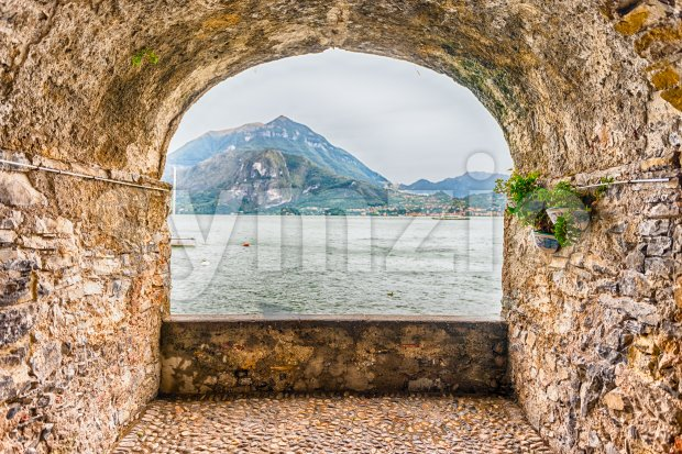 Scenic rock arch balcony overlooking the Lake Como and the town of Menaggio in distance, Varenna, Italy